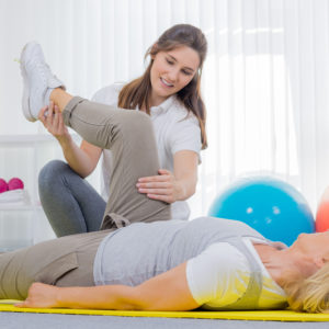 seniorin bekommt hilfestellung bei der gymnastikübung